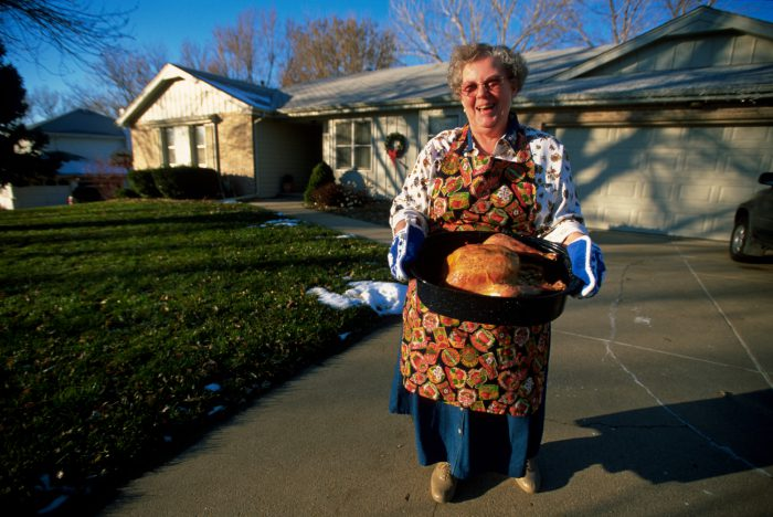 Photo: A woman displays her Thanksgiving turkey outside her home.