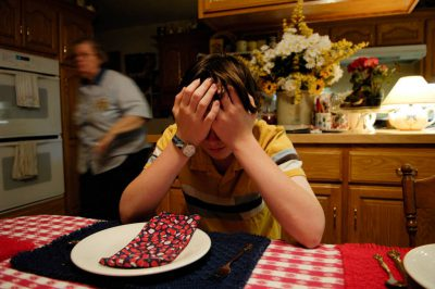 Photo: A teenager looks disappointed at the dinner table.