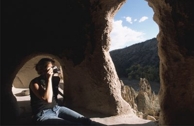 Photo: A woman takes a photograph of ancient Indian cliff dwellings.