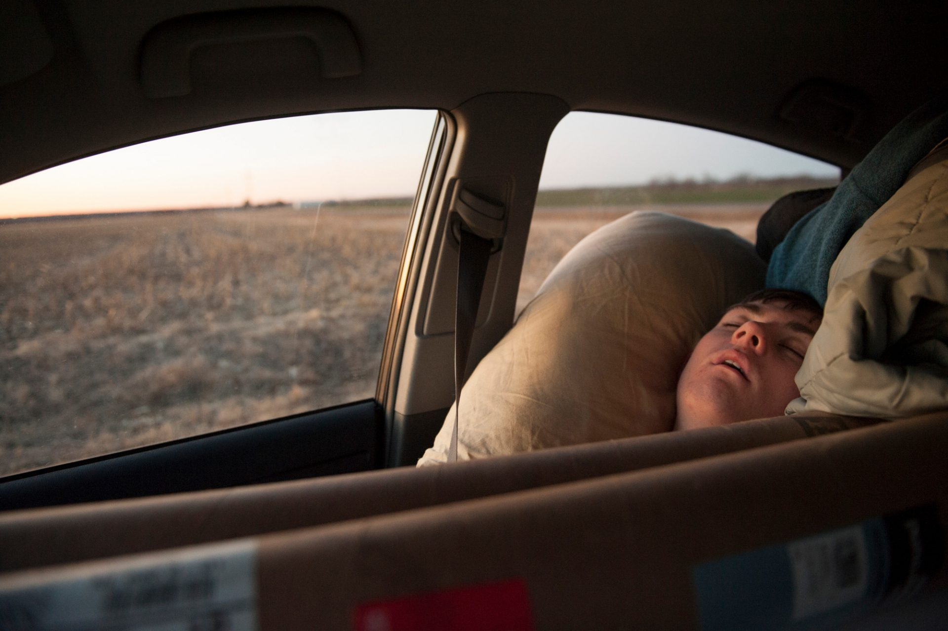 Photo: Cole Sartore sleeps jammed next to rolls of background paper on a road trip.