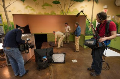 Joel Sartore and a news crew from NBC Nightly News prepare to photograph a West African dwarf crocodile (Osteolaemus tetraspis tetraspis) at the Lincoln Children's Zoo.