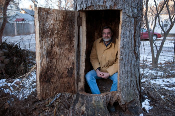 Photo: A man sits inside of a hollowed out tree he built in Lincoln, Nebraska.