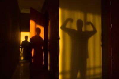 Photo: Three shadowy figures on a hallway.