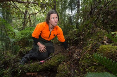 Photo: A woman searching for rowi kiwi nests in a forest on Lake Mapourika near Franz Josef Glacier, New Zealand.