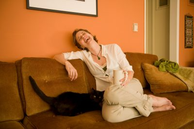 Photo: A woman sits on her couch with her cat.