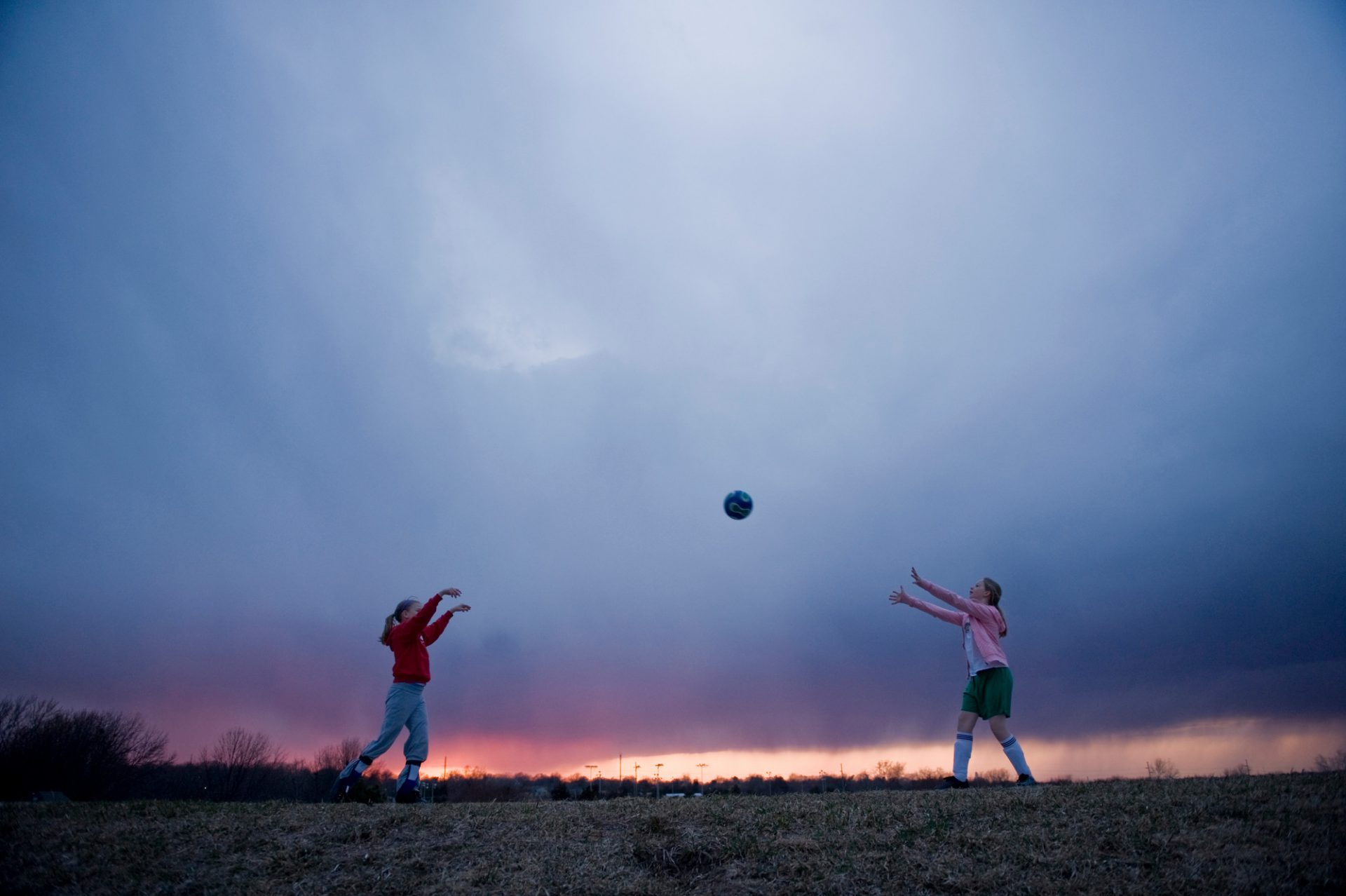 Photo: Two young girls play volleyball atop a dam.