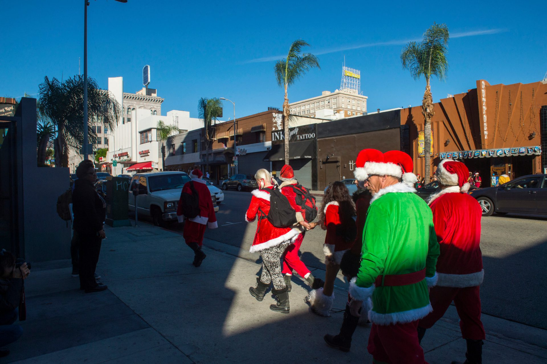 Photo: Men and women wearing Santa Claus and Mrs. Claus costumes walk on the sidewalk in Hollywood.