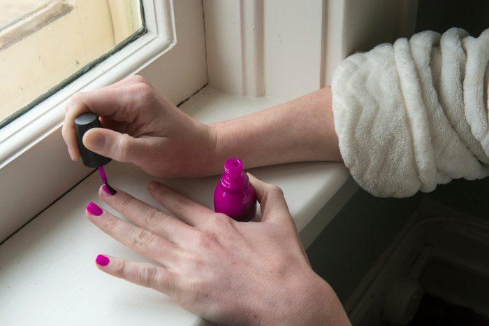 Photo: A young woman paints her fingernails.