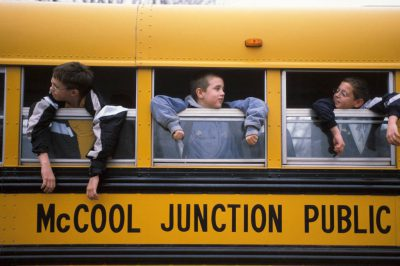 Photo: Students lean out of bus windows after school in McCool Junction, Nebraska.