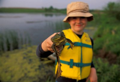 Photo: Cole Sartore holds up a frog caught on a fishing trip.