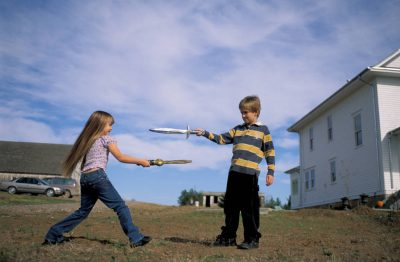 Photo: Two children sword-fighting on the family's farm.