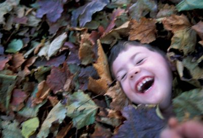 Photo: Cole Sartore buried in fall leaves.
