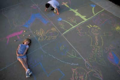 Photo: Cole and Ellen Sartore amid chalk drawings on the driveway.