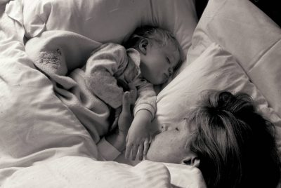 Photo: A boy and his mother, asleep.