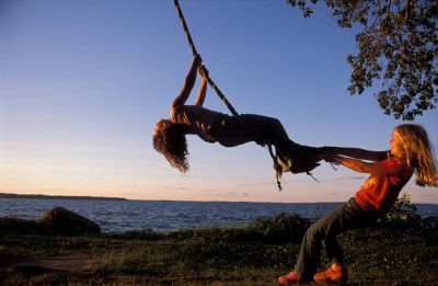 Photo: Ellen and Shannon play on a rope swing at the edge of Leech Lake in Minnesota.