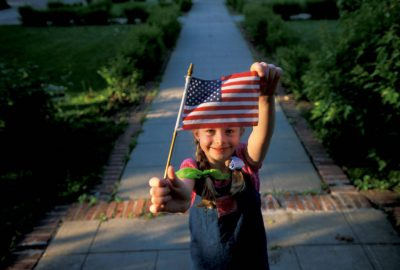 Photo: Ellen Sartore holds up an American flag outside her home inLincoln, Nebraska.