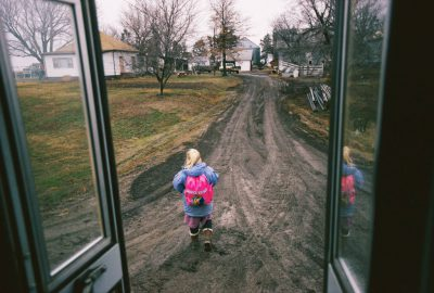 Photo: A girl gets off the bus and into a muddy driveway in McCool Junction, NE.