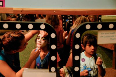 Photo: A volunteer at the Lincoln Children's Museum applies face paint to a young girl.