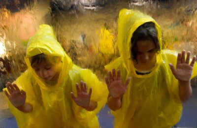 Photo: Children look through a piece of glass while water falls over them at the Lincoln Children's Museum in Nebraska.