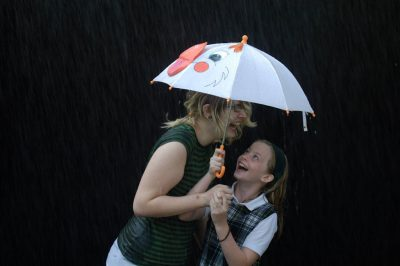 "Photo: Ellen and Jordan crowd under a tiny umbrella to ""rain"" from a sprinkler in Lincoln, NE."