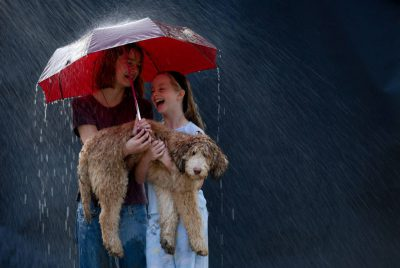 "Photo: Emma, Ellen and Muldoon the dog play in the ""rain"" from a sprinkler in Lincoln, NE."