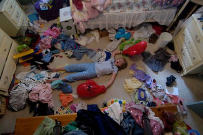Photo: A young girl lies in her messy room.