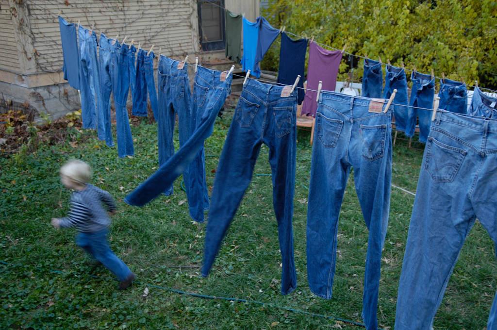 Photo: A little boy runs through jeans that hang on a clothes line.