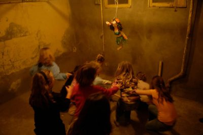 Photo: Girls fight for candy from a pinata at a ten-year-old's birthday party.