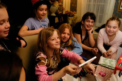 Photo: A girl opens presents with friends at her tenth birthday party.