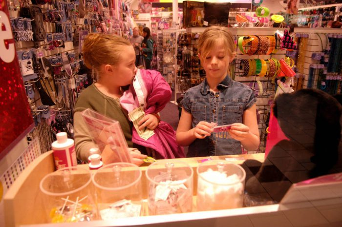 Photo: A young girl get her ears pierced at a mall.
