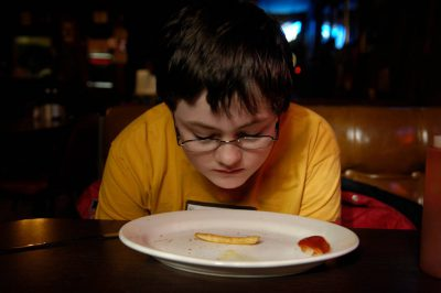 Photo: A young boy eats lunch at a restaurant in Anselmo, NE.