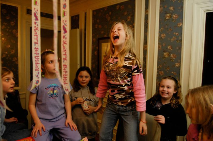 Photo: A girl opens presents with friends at her 10th birthday party.