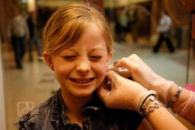 Photo: A young girl gets her ears pierced at a mall.