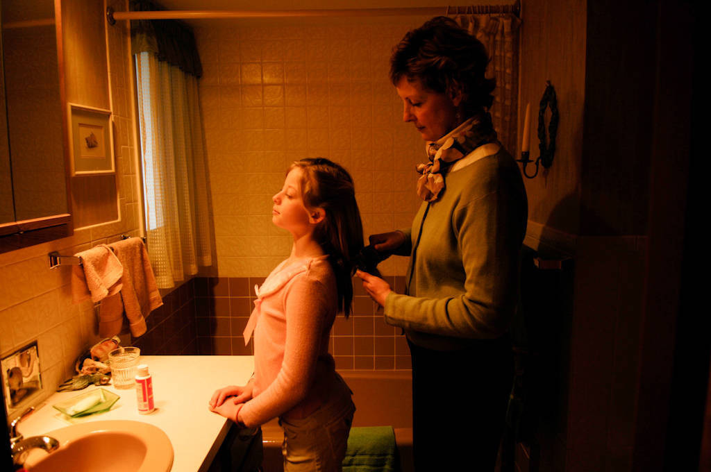 Photo: A mother brushes her daughter's long blonde hair.