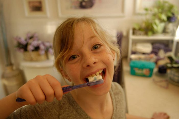 Photo: A young girl brushes her teeth.