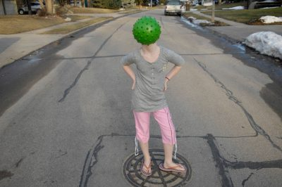 Photo: A young girl plays with a green ball.