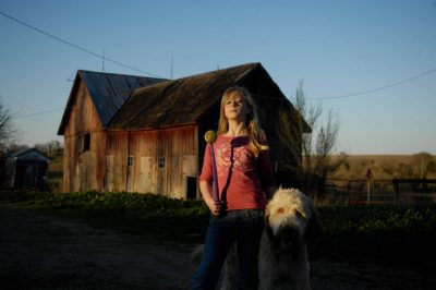 Photo: A girl stands near a barn with her pet dog, Muldoon.
