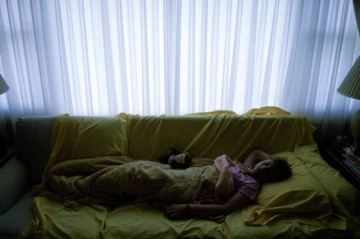 Photo: A young girl sleeps on a couch.