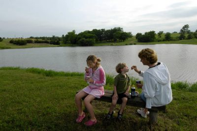 Photo: A mother feeds her two young children at a scout camp near Humbolt, Nebraska.