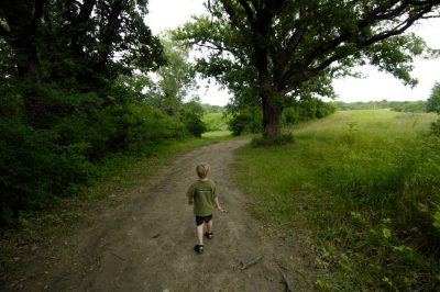 Photo: A three-year-old runs down a dirt road at a scout camp near Humbolt, Nebraska.