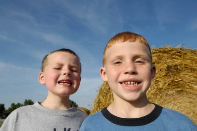 Photo: Two young kids pose in front of a haybale in Greenleaf, Kansas.