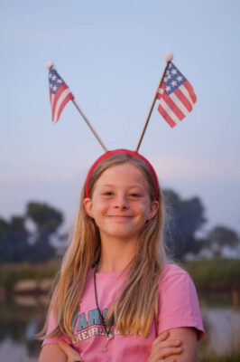 Photo: A young girl shows her patriotism during the July 4th celebration at the Fenton Farm near Greenleaf, KS.