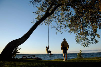 Photo: Children play on a rope swing along the shores of Leech Lake, MN.