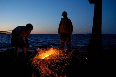 Photo: Children sit around campfire along the shores of Leech Lake, MN.