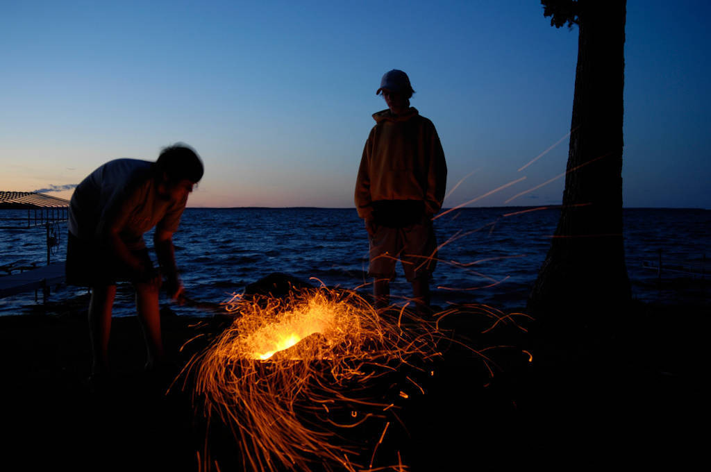 Photo: Children sit around campfire along the shores of Leech Lake, MN.