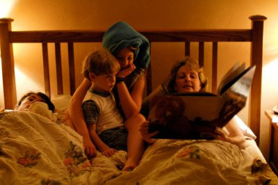 Photo: A mother reads a bedtime story to her children.