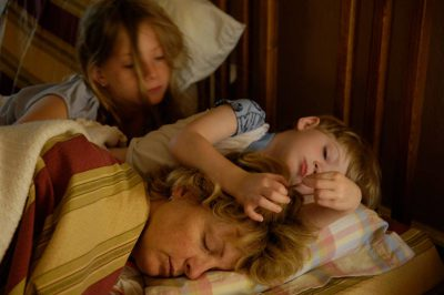 Photo: A mother sleeps while her three-year-old is a pest.