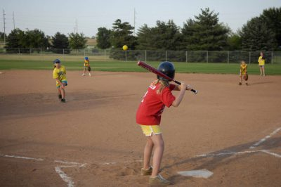 Photo: A young girl swings a bat while playing softball with a YMCA league.