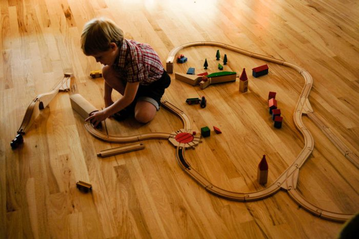 Photo: A three-year-old plays with a train set on a wood floor.