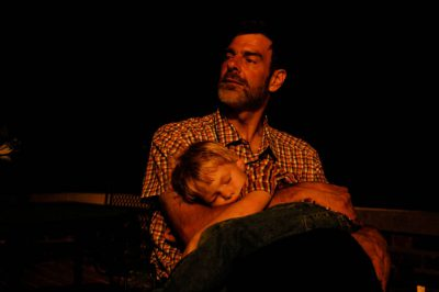 Photo: A man holds his exhausted young son.